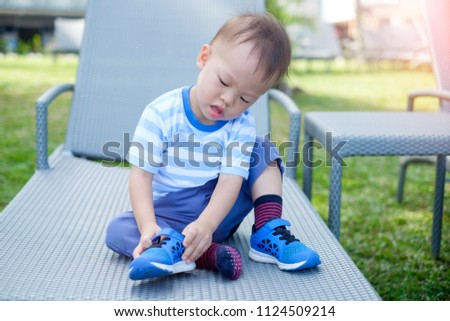 Cute little Asian 18 months / 1 year old toddler boy child sitting and concentrate on putting on his own blue shoes / sneakers, Encourage Self-Help Skills in Children, Develop Confidence concept
