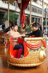 Cute little Asian siblings having fun on a carousel.