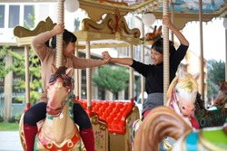 Cute little Asian siblings having fun on the horse of merry-go-round.