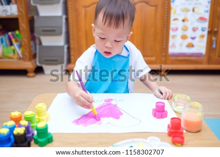 Cute little Asian 2 years old toddler baby boy child painting with paint brush & watercolors, Kid drawing pink heart, making Mothers day card, Creative play for toddlers & Happy Mother's Day concept