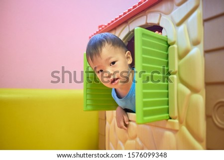 Cute little Asian 2 years old toddler boy child is playing peek a boo from the window of plastic toy house, Kids indoor playground, Indoor play areas for Children's Early Development concept
