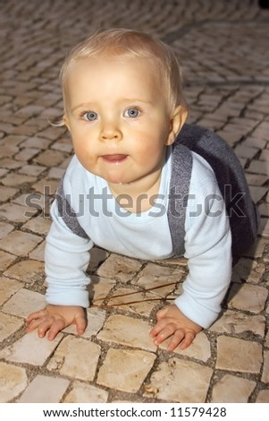 Cute little baby boy crawling on the tiles