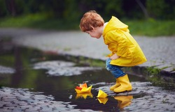 cute little baby boy launching paper boats in spring puddles, wearing raincoat and rubber boots