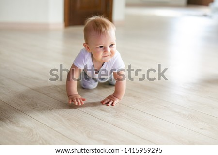 Cute little baby boy lying on hardwood and smiling. Child crawling over wooden parquet and looking up with happy face. View from above. Copyspace.