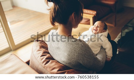 Cute little baby boy smiling in his mother's hands. Woman sitting on sofa with her smiling baby at home.