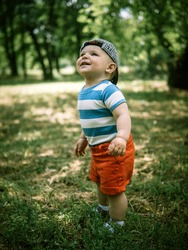 Cute little baby boy walks through the summer park. Child is laughing. Adorable baby boy in a baseball cap. Baby boy runs on the green grass for soap bubbles.  Happy child in the forest.