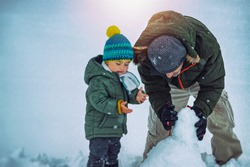 Cute Little Baby Boy with Father Having Fun Outdoors in Winter Time. With Pleasure Build Snowman. Enjoying Winter Holidays Together.