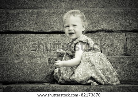 Cute Little baby find something on the ground - outdoors. B&W version - stock photo