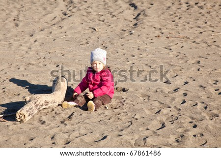 Cute little baby girl having fun on the beach.