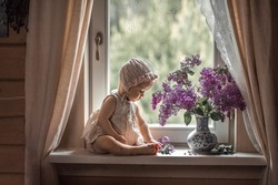 Cute little baby girl in a bonnet on the windowsill looking at beautiful lilac bouquet in a vase. Image with selective focus and toning