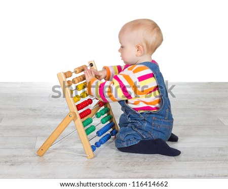 Cute little baby girl kneeling on the floor in dungarees playing with a colorful abacus moving the counters as she learns