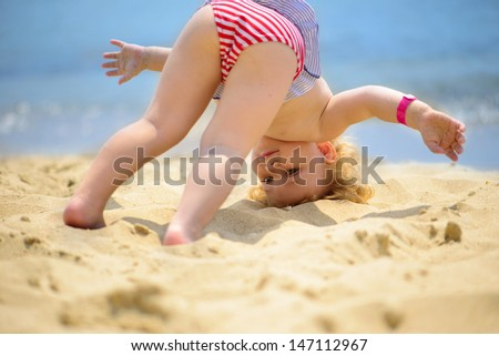 Cute little baby girl making yoga exercises at ocean beach