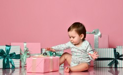 Cute little baby girl surrounded by heaps of gifts in pink boxes with bows. on a pink pastel background. Birthday and girlhood concept
