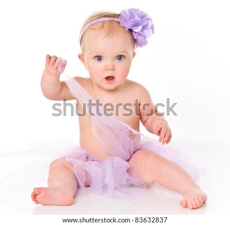Cute little baby girl with big blue eyes wearing a tutu and flower in her hair