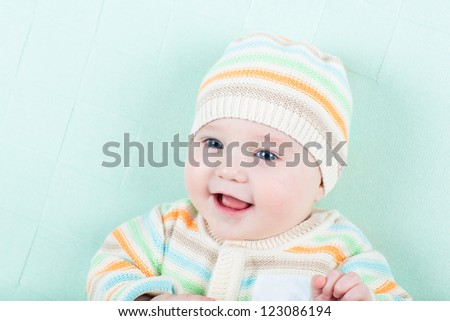 Cute little baby in a knitted jacket and hat on a green blanket