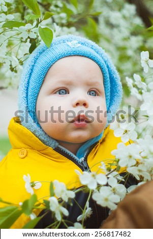 cute little baby in blue hat over spring blossom trees background. beautiful boy with blue eyes. parenting or love concept. children and parents in park. adorable child, infant, kid. family lifestyle - stock photo