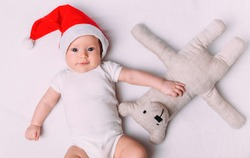 Cute little baby in Santa hat on soft fabric. Baby first christmas. Santa baby. New Year's holidays.