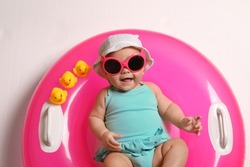 Cute little baby in sunglasses with inflatable ring on white background, top view