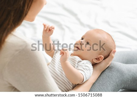 Cute little baby looking at mother while lying on her laps, over shoulder view #1506715088