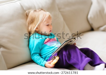 Cute little baby or toddler girl reading a book on a leather couch indoors on a rainy day