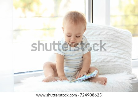 Cute little baby with book sitting on window sill at home