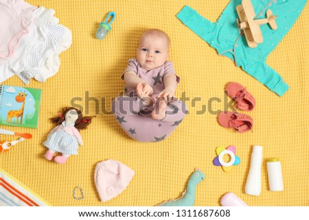 Cute little baby with clothing and accessories on color blanket, top view