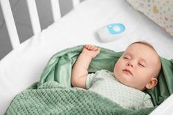 Cute little baby with radio nanny sleeping in crib