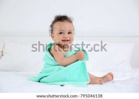Cute little baby with towel after bathing on bed at home