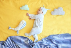 Cute little baby with toys sleeping on bed at home