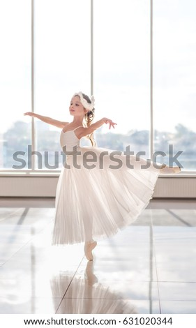 Cute little ballerina in white ballet costume and pointe shoes with is dancing in the room. Kid and Ballet dance. Child girl is studying ballet.  Copyspace.