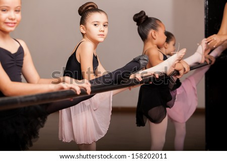 Cute little ballet dancers practicing some dance moves in a barre in a dance class