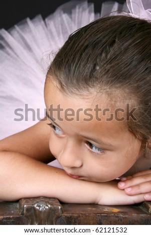 Cute little ballet girl wearing a tutu lying on an antique trunk