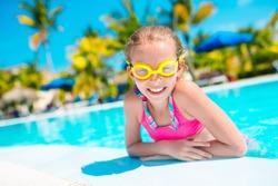 Cute little beautiful girl swims in outdoor swimming pool