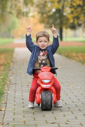 cute little biker on road with motorcycle. Young boy on toy motorcycle