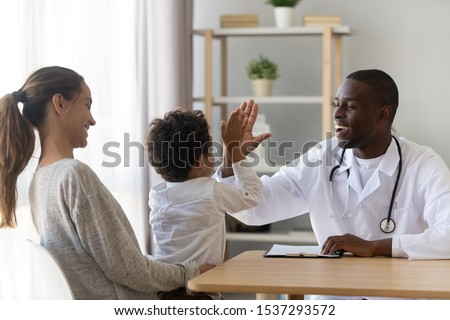 Cute little biracial boy give high five to positive african American male doctor visiting with mom, small toddler child make deal celebrate good medical checkup or greeting with smiling pediatrician