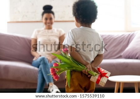 Cute little biracial toddler boy kid stand hiding flowers bouquet and gift making birthday surprise for young mother, small african American child son give present congratulate mom with anniversary