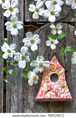Cute little birdhouse on rustic wooden fence with beautiful white Dogwood blooms on them