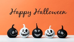 Cute Little Black and White Halloween Pumpkins with smile standing side by side on white wooden table over orange background. Halloween concept.