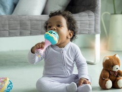 Cute little Black baby boy putting rattle toy into mouth.