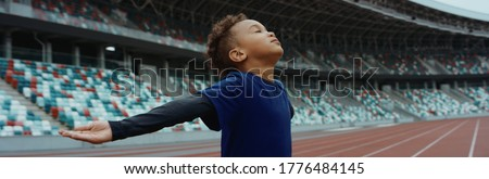 Cute little black kid boy spreading his hands on an empty stadium, dreaming of becoming professional player, soccer star Photo stock ©