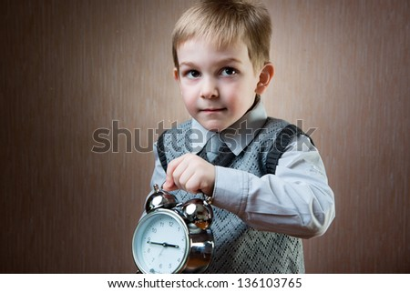 Cute little blond boy holding alarm clock