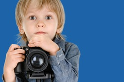 Cute little blond boy using professional digital camera