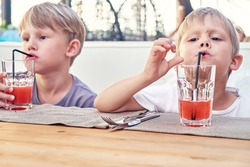 Cute little blond brothers drink fresh strawberry juice with straws sitting at wooden table in cafe in summer evening close view