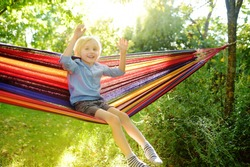 Cute little blond caucasian boy having fun with multicolored hammock in backyard or outdoor playground. Summer active leisure for kids. Child on hammock. Activities and fun for children outdoors