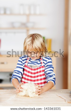 Cute little blond girl baking cookies standing at the kitchen counter knead pastry or dough