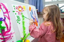 Cute little blond girl holding the brush and painting on the paper