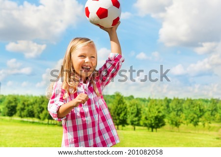 Cute little blond girl in pink shirt throwing soccer ball laughing