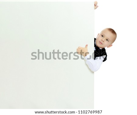 6e982baf4198 Cute little blonde boy in a black waistcoat and a white shirt and a bow at