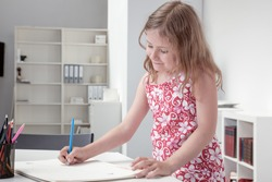 Cute little blonde girl in a pretty floral summer dress smiling happily as she stands at a table sketching on a large sketchpad
