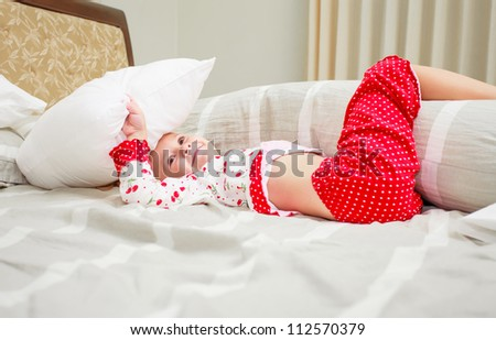 Cute little blonde girl in her pajamas holding a pillow
